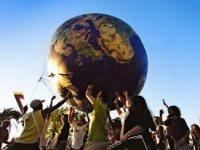 People outside supporting a large globe above their heads.